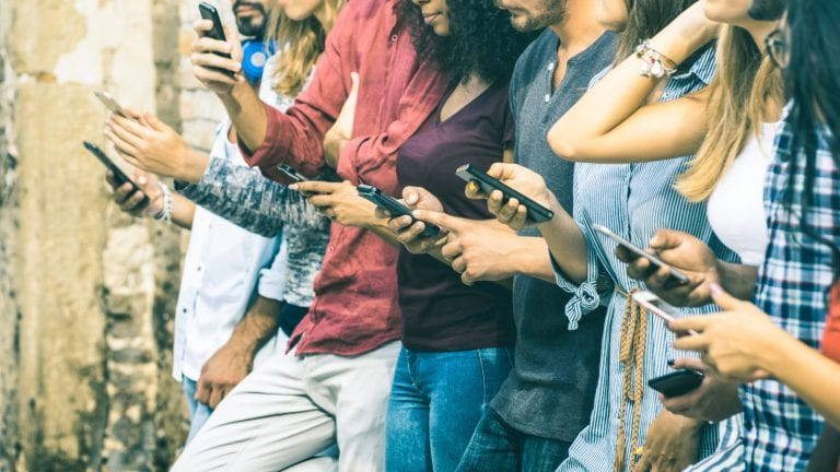 a group of young people all looking at their phones